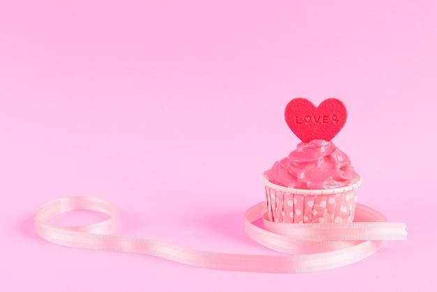 Cupcake caseiro doce com coração vermelho em forma de fondant sobre fundo rosa