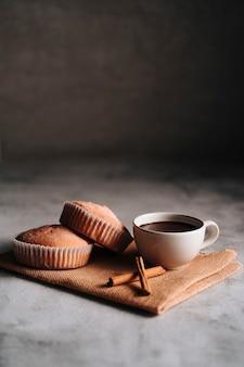 Cupcake com açúcar de confeiteiro sobre um pano de fibra com chocolate quente e alguns pedaços de canela. copie o espaço.