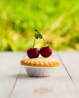 Cupcake com cerejas em placas de madeira brancas Foto Premium