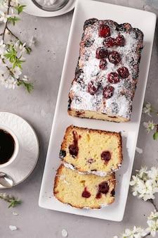 Cupcake com cerejas em um prato branco sobre um concreto cinza e uma xícara de café
