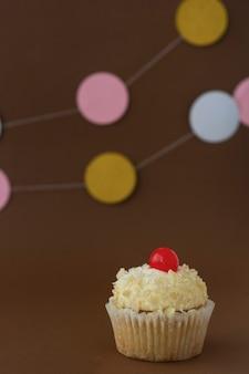 Cupcake com creme de manteiga de baunilha, fundo marrom com caixas de presente, conceito de aniversário. sobremesa doce.