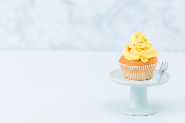Cupcake com decoração creme amarela em stand vintage no fundo pastel azul.