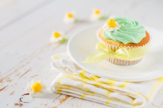 Cupcake com fita amarela na mesa de madeira branca