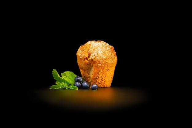 Cupcake com mirtilos e folhas de hortelã, polvilhadas com açúcar de confeiteiro