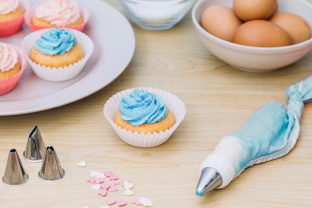 Cupcake com saco de confeiteiro; polvilhe; bocal na mesa de madeira