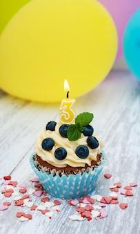 Cupcake com um numeral de três velas