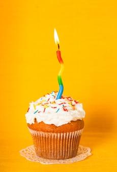 Cupcake com uma vela acesa em um guardanapo amarelo