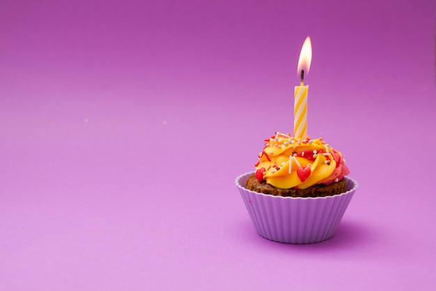 Cupcake com uma vela e corações em uma superfície lilás. . conceito dia dos namorados