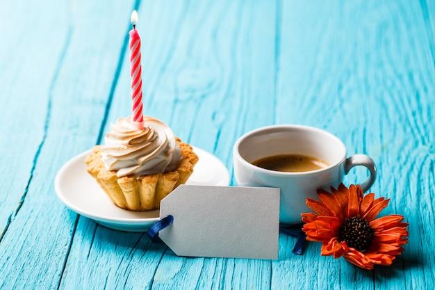 Cupcake com vela perto de café e flor