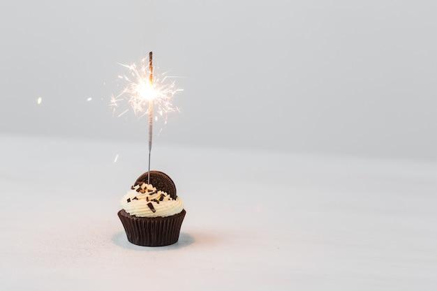 Cupcake de aniversário com diamante sobre fundo branco.