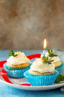 Cupcake de aniversário com papoula de chantilly e casca de laranja em um fundo azul copie o espaço