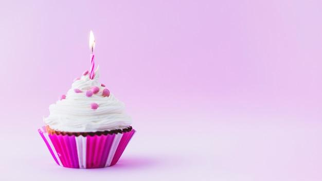 Cupcake de aniversário com vela iluminada no fundo roxo