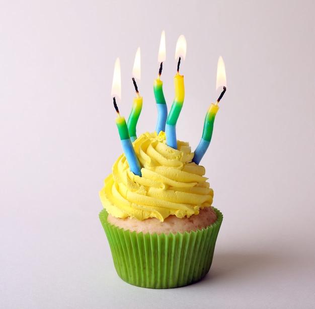 Cupcake de aniversário com velas na superfície colorida