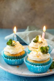 Cupcake de aniversário de laranja com cobertura de creme de manteiga e vela copie o espaço