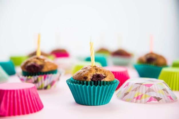 Cupcake de aniversário nos suportes de papel com velas