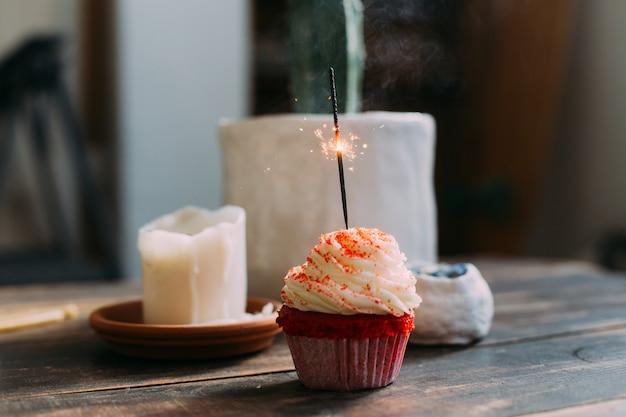 Cupcake de aniversário rosa com vela brilhante