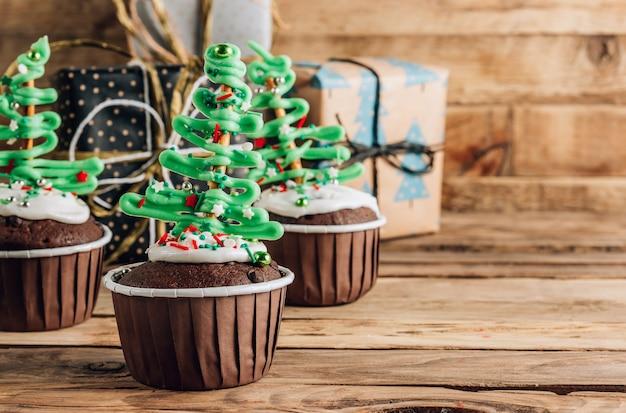 Cupcake de árvore de natal de chocolate com cobertura de açúcar colorida