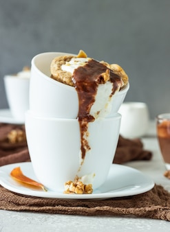 Cupcake de cenoura ou abóbora com chantilly, molho de caramelo e nozes em uma caneca de cerâmica branca.