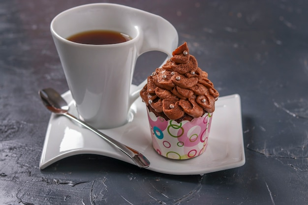 Cupcake de chocolate caseiro com creme e uma xícara de café em uma superfície escura, closeup, orientação horizontal