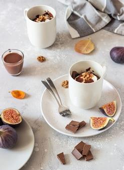 Cupcake de chocolate com queijo creme ou ricota com molho de caramelo em uma caneca de cerâmica branca. comida de outono ou inverno de conforto.