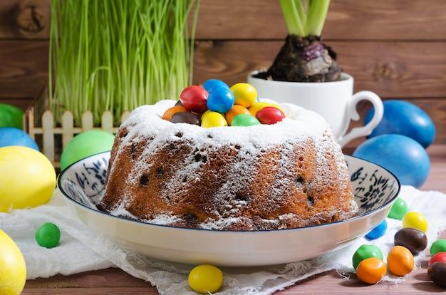 Cupcake de páscoa com açúcar em pó e pastelaria em fundo rústico de madeira