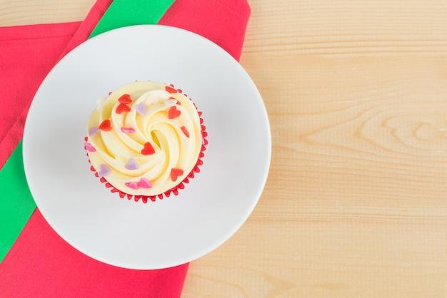 Cupcake de veludo vermelho com fita verde xmas na placa de madeira
