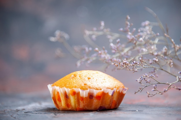 Cupcake de vista lateral close-up um cupcake apetitoso na mesa e galhos de árvores