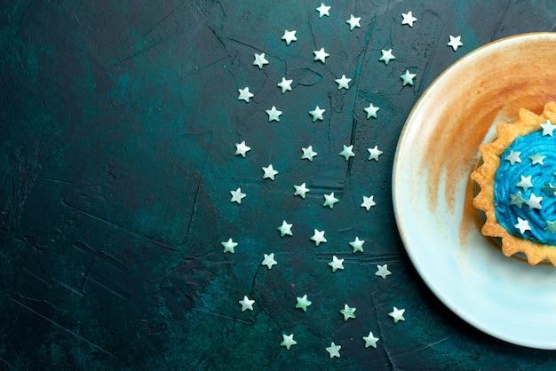 Cupcake de vista lateral com decoração de estrelas ao lado de estrelas azuis escuras,