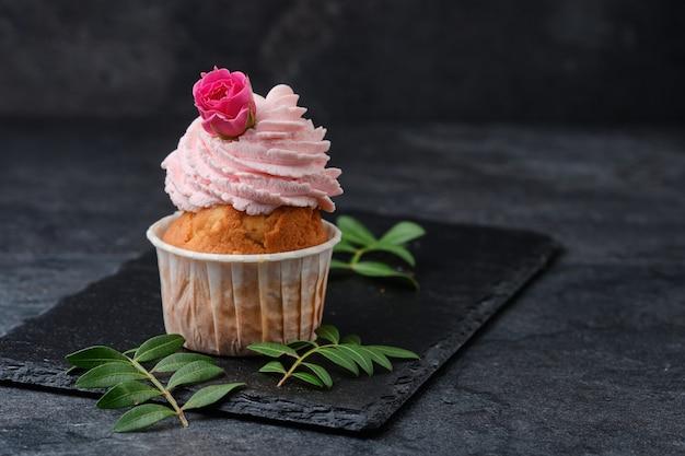 Cupcake decorado com rosas. sobremesa em um prato de ardósia preta. bolos em um fundo escuro.