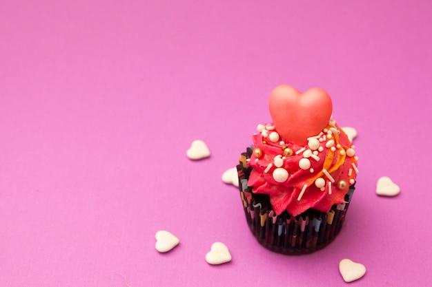 Cupcake dia dos namorados. cupcake decorado com creme e coração. feliz dia dos namorados conceito