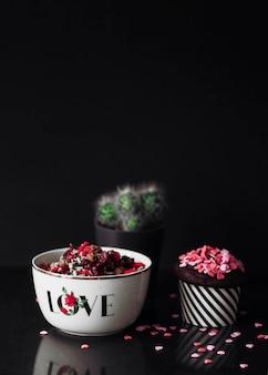 Cupcake e frutas secas na tigela em fundo preto