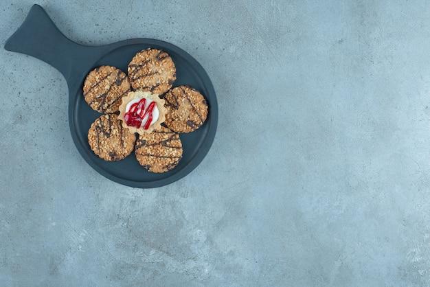 Cupcake rodeado de biscoitos em uma pequena assadeira sobre superfície de mármore