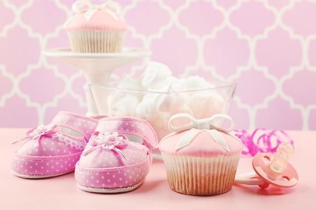 Cupcake saboroso com laço e sapatilhas de bebê, chupeta