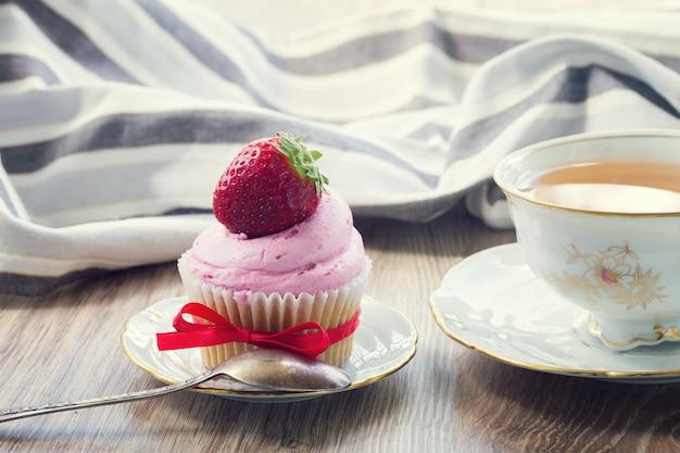 Cupcake vintage com morango fresco no prato e xícara de chá na mesa de madeira