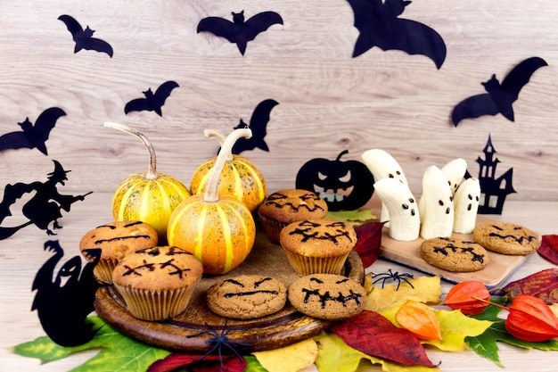 Cupcakes assustadores, abóbora, folhas e silhueta de morcego em pratos de madeira