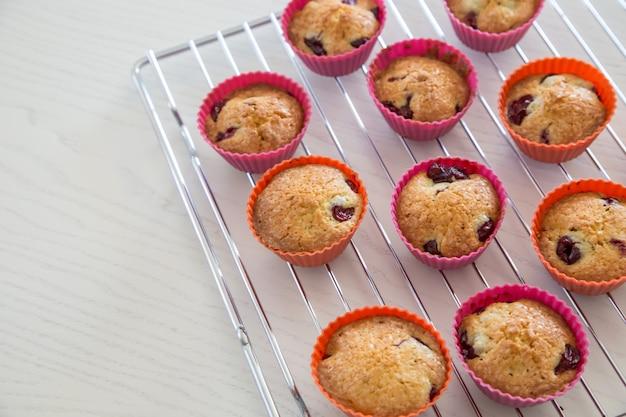 Cupcakes caseiros com cereja, muffins em uma cremalheira de fio em uma mesa branca