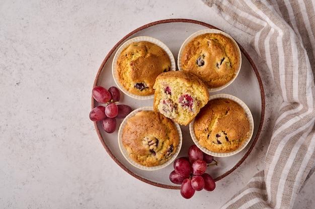 Cupcakes caseiros com cerejas e uvas no prato com guardanapo na cópia de vista superior de fundo claro