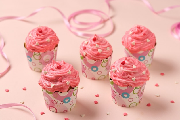 Cupcakes caseiros com creme em um fundo rosa.