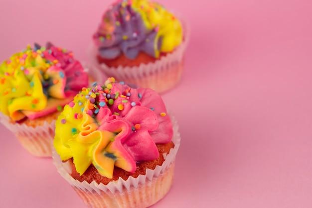 Cupcakes caseiros com creme multi-colorido em um espaço de cópia de fundo rosa. creme amarelo e rosa.