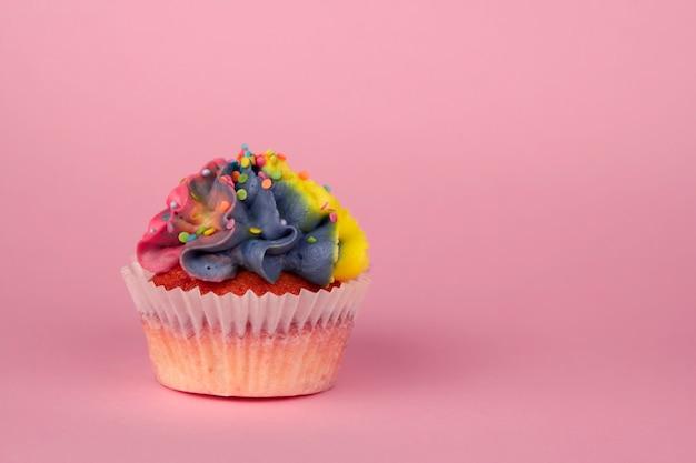 Cupcakes caseiros com creme multi-colorido em um espaço de cópia de fundo rosa.