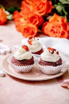 Cupcakes caseiros de veludo vermelho com chantilly em um prato de cerâmica rosa, guardanapo branco com fita, flores rosas, corações de madeira sobre parede de textura rosa