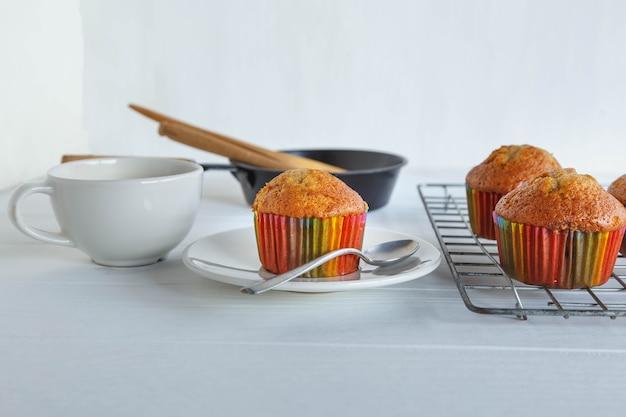 Cupcakes caseiros e xícara de café na mesa branca