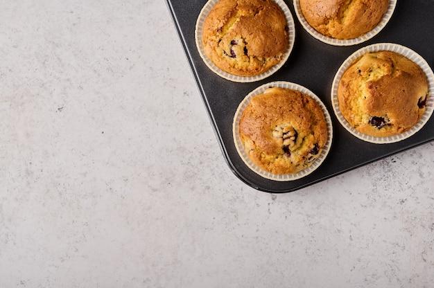 Cupcakes caseiros em forma de cozimento no espaço de cópia da vista superior de fundo cinza de madeira