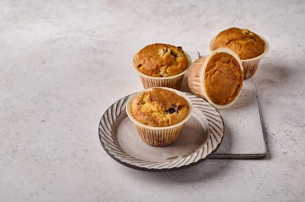 Cupcakes caseiros em formas de papel manteiga no prato e tábua de cerâmica riscada na cor cinza
