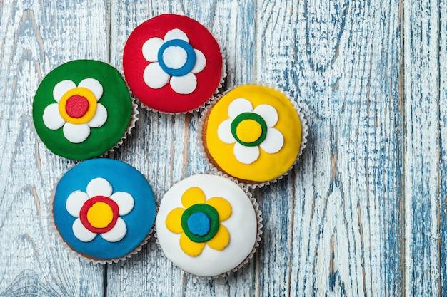 Cupcakes cobertos com mástique em uma mesa de madeira