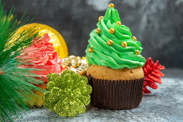 Cupcakes coloridos de frente, brinquedos para árvores de natal em cinza