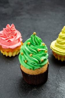Cupcakes coloridos de frente no escuro