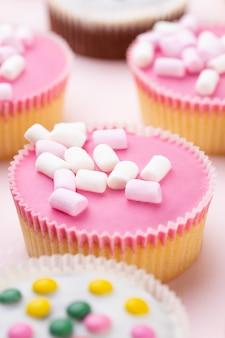Cupcakes coloridos em um fundo rosa.