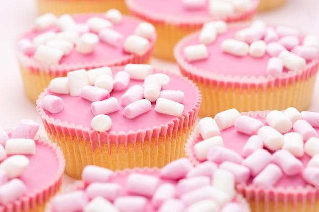 Cupcakes coloridos em um fundo rosa