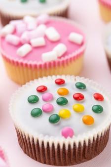 Cupcakes coloridos em uma rosa.